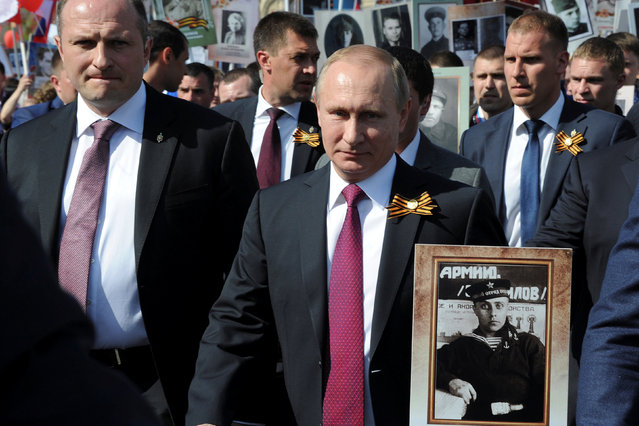 Russian President Vladimir Putin (C) holds the portrait of his father, war veteran Vladimir Spiridonovich Putin, as he takes part in the Immortal Regiment march during Victory Day celebrations marking the 71st anniversary of the victory over Nazi Germany in World War Two, at Red Square in Moscow, Russia, May 9, 2016. (Photo by Mikhail Klimentyev/Reuters/Sputnik/Kremlin)