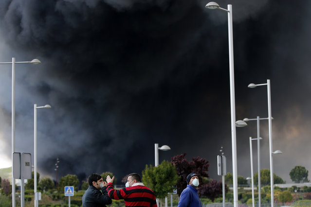 Men with masks talk in front of billowing black smoke from a huge fire in Sesena, central Spain, Friday, May 13, 2016. (Photo by Paul White/AP Photo)