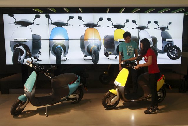 A woman tries to ride a Gogoro Smartscooter in its shop in Taipei, Taiwan, July 6, 2015. (Photo by Pichi Chuang/Reuters)