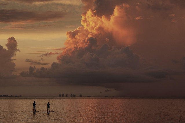 Two paddle boarders stop to watch the sunrise on a stormy morning in Sanibel, Fla., Thursday, August 15, 2019. (Photo by J. David Ake/AP Photo)