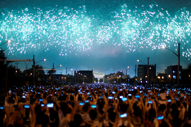 People on the street hold their phones as fireworks explode in the sky during an evening gala marking the 70th anniversary of the founding of the People's Republic of China, on its National Day in Beijing, China on October 1, 2019. (Photo by Aly Song/Reuters)