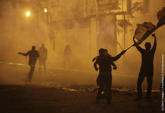 Protesters run through clouds tear gas fired by security forces in Cairo, Egypt