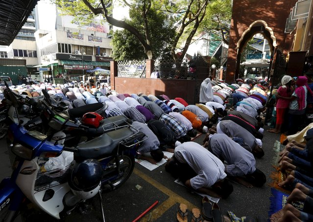 Foreign workers pray on the street outside a mosque during Eid Al-Fitr prayers in Kuala Lumpur, Malaysia, July 17, 2015. (Photo by Olivia Harris/Reuters)