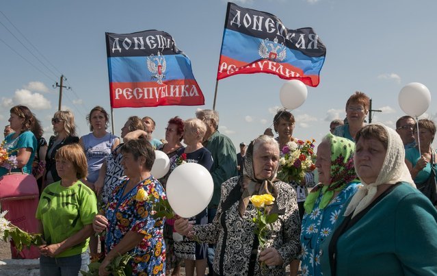Local residents holding flowers and flags of the self-proclaimed Donetsk People's Republic attend a memorial ceremony at the crash site of the Malaysian Airlines MH17 plane near the village of Hrabove, eastern Ukraine, Friday, July 17, 2015. (Photo by Antoine E. R. Delaunay/AP Photo)