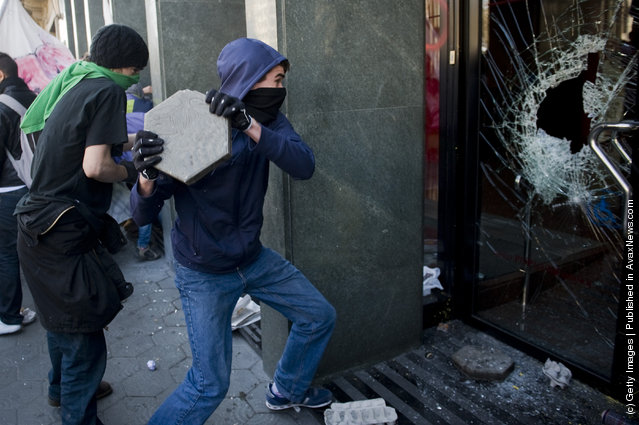 A student throws a stone at the window of a bank during a demonstration on February 29, 2012 in Barcelona