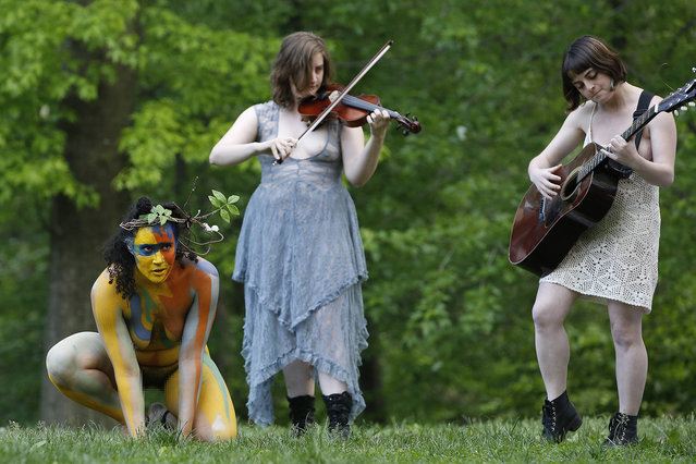 "Reanna Roane, left, creeps out of the woods as she joins an all-female cast of 13 actors, musicians and dancers during the Outdoor Co-ed Topless Pulp Fiction Appreciation Society theater company's performance of Shakespeare's ""The Tempest"", in Central Park, Thursday, May 19, 2016, in New York. The stripped-down production celebrates body freedom and expression using full and semi-nudity to dramatize the conflict between the visitors to Prospero's island and its inhabitants. (Photo by Kathy Willens/AP Photo)"