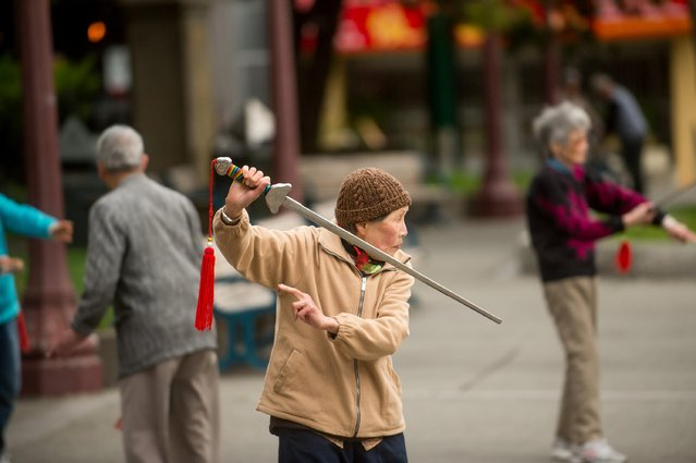 In this June 9, 2015 photo, a woman practices Tai Chi in San Francisco's Chinatown. The country's oldest Chinatown has sheltered immigrants for more than 100 years, but may face changes as San Francisco undergoes an unprecedented boom in technology jobs. (Photo by Noah Berger/AP Photo)