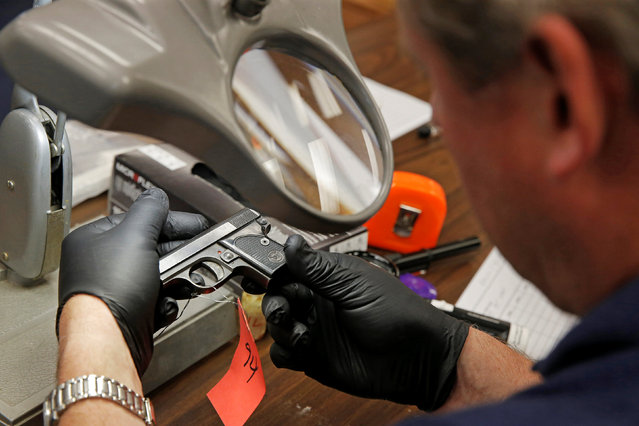 "A Chicago Police officer examines a gun turned in from the public as part of the ""Gun Turn-in"" event where a gift card is given for every firearm turned over to police at Universal Missionary Baptist Church in Chicago Illinois, U.S. May 28, 2016. (Photo by Jim Young/Reuters)"
