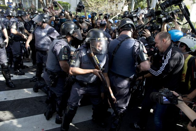 Police shouts at journalists covering the detention of a protestor in Sao Paulo, Brazil, Thursday, June 12, 2014. (Photo by Rodrigo Abd/AP Photo)