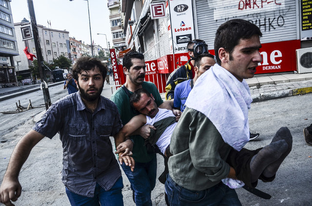 Protesters carry a wounded man in Istanbul, Saturday, July 25, 2015, during clashes between police and protesters denouncing the deaths of 32 people at an suicide bombing Monday in Suruc, southeastern Turkey. Turkish jets struck camps belonging to Kurdish militants in northern Iraq, authorities said Saturday, the first strikes since a peace deal was announced in 2013, and again bombed Islamic State group positions in Syria. (Photo by Cagdas Erdogan/AP Photo)