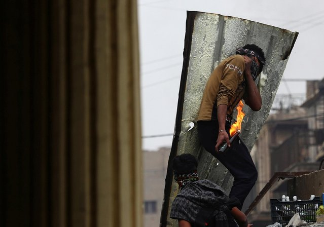 A demonstrator holds a Molotov cocktail during the ongoing anti-government protests in Baghdad, Iraq on November 25, 2019. (Photo by Thaier al-Sudani/Reuters)