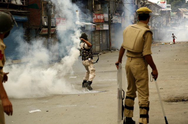 An Indian policeman throws an exploded tear smoke shell on Kashmiri protesters   during a protest in Srinagar, India, Sunday, July 26, 2015. Indian Security forces fired tear gas and rubber bullets Sunday to disperse angry protesters after the dead body of a youth was found in a river under mysterious circumstances. Anti-India sentiment runs deep in the Indian-administered Kashmir, where rebel groups have fought since 1989 for independence or merger with Pakistan. (Photo by Mukhtar Khan/AP Photo)