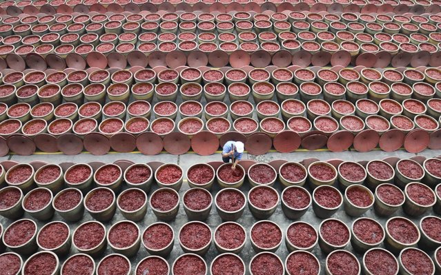 A worker dries bean sauce stored in vats at a factory on November 16, 2019 in Chengdu, Sichuan Province of China. (Photo by Zhang Lang/China News Service/VCG via Getty Images)