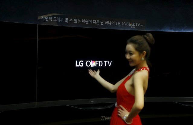 A model poses for photographs with LG Electronics Inc's Super Ultra HD Television sets during its launch event at company's headquarters in Seoul in this February 24, 2015 file photo.  LG Electronics is expected to release Q2 earnings this week. (Photo by Kim Hong-Ji/Reuters)