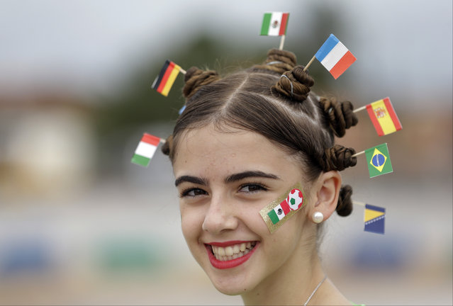 A fan with the flags of Italy, Germany, Mexico, the Netherlands, Spain, Brazil and Bosnia in her hair smiles prior to the group A World Cup soccer match between Brazil and Mexico at the Arena Castelao in Fortaleza, Brazil, Tuesday, June 17, 2014. (Photo by Themba Hadebe/AP Photo)