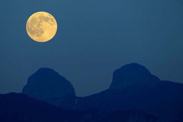 The full moon rises above the Tour de Mayen and Tour d'Ai in the Swiss Alps in this picture taken from Chardonne near Vevey, Switzerland, July 1, 2015. (Photo by Denis Balibouse/Reuters)