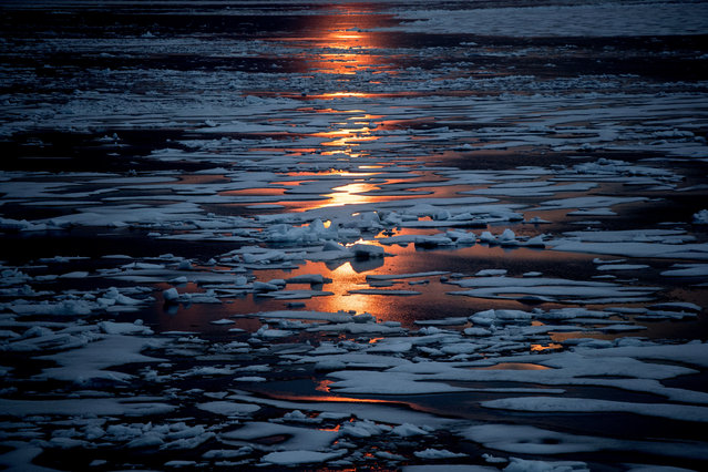 In this July 23, 2017, file photo the midnight sun shines across sea ice along the Northwest Passage in the Canadian Arctic Archipelago. The magnetic north pole is wandering about 34 miles (55 kilometers) a year. At the end of 2017 it crossed the international date line. That means it's not even the same day at the new magnetic north pole as it is at the spot of 2010's magnetic north pole. It's leaving the Canadian Arctic on its way to Siberia. (Photo by David Goldman/AP Photo)
