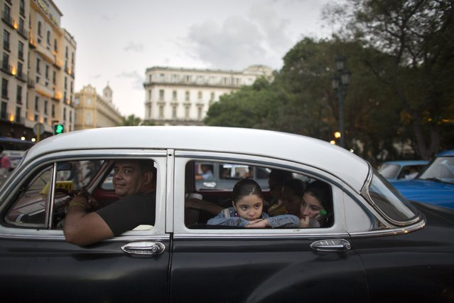 A girl peers from the window of a vintage car used as a collective taxi in downtown Havana February 9, 2015. (Photo by Alexandre Meneghini/Reuters)