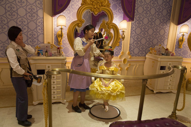 "A Chinese girl gets a Princess makeover at the Disney Resort in Shanghai, China, Wednesday, June 15, 2016. The debut of Shanghai Disneyland offers Walt Disney Co. ""incredible potential"" for boosting its brand in the world's most populous market, Disney's chief executive said Wednesday ahead of Thursday's grand opening for the $5.5 billion park. (Photo by Ng Han Guan/AP Photo)"