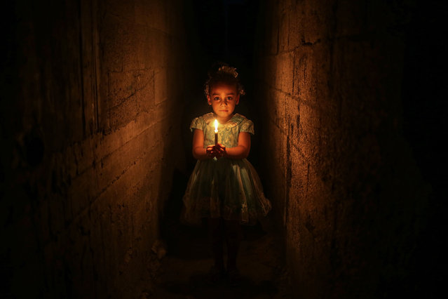 A Palestinian girl holds a candle to lighten her home due to power cut at the Jabalia Camp in Gaza City, Gaza on June 27, 2017. 2 million people living in Gaza suffering power cut as the Israeli siege continues. (Photo by Ali Jadallah/Anadolu Agency/Getty Images)