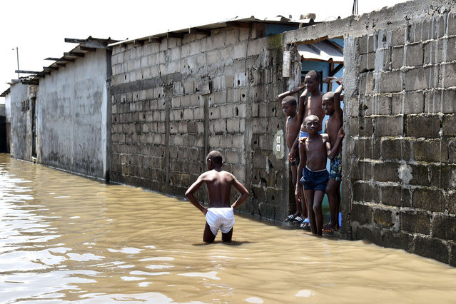 Young boys stand in a street flooded by rain water in the impoverished neighborhood of Adjouffou in Abidjan, Ivory Coast, on July 9, 2014. Several weeks of torrential rainfall in the Ivorian economic capital have left several people dead and caused substantial damage to the city and other areas of the country. (Photo by Issouf Sanogo/AFP Photo)