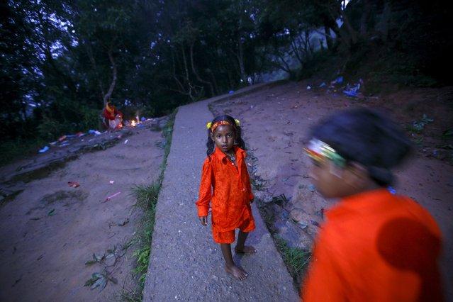 "Children on pilgrimage walk along the woods during the ""Bol Bom"" pilgrimage in Kathmandu August 10, 2015. (Photo by Navesh Chitrakar/Reuters)"