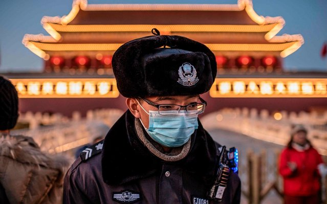 A police officer wearing a protective mask walks past the portrait of late communist leader Mao Zedong (not pictured) at Tiananmen Gate in Beijing on January 23, 2020. Large-scale Lunar New Year events in Beijing have been cancelled as part of national efforts to control the spread of a new SARS-like virus, city authorities announced on January 23. (Photo by Nicolas Asfouri/AFP Photo)