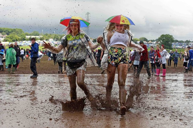 Festival goers splash through a muddy puddle at Worthy Farm in Somerset, on the third day of the Glastonbury music festival June 27, 2014. (Photo by Cathal McNaughton/Reuters)