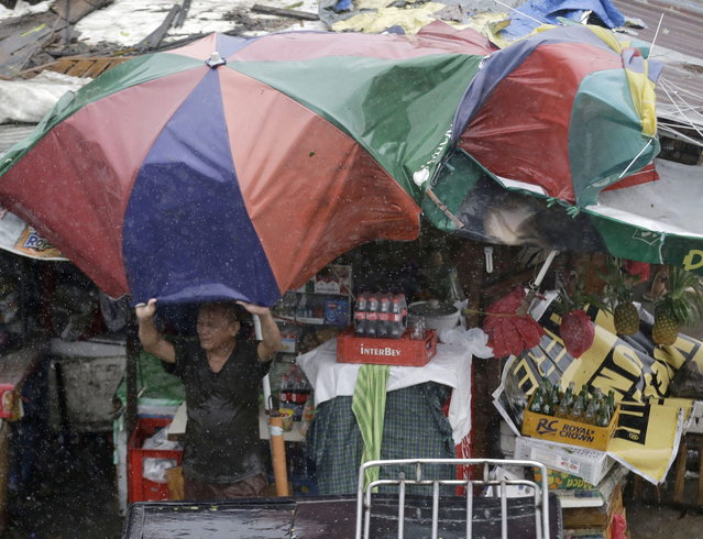 A man holds a large umbrella at the onslaught of Typhoon Rammasun (locally known as Glenda) which battered Taguig city east of Manila, Philippines Wednesday, July 16, 2014. Typhoon Rammasun left at least seven people dead and knocked out power in many areas but it spared the Philippine capital, Manila, and densely populated northern provinces from being directly battered Wednesday when its fierce wind shifted slightly away, officials said. (Photo by Bullit Marquez/AP Photo)