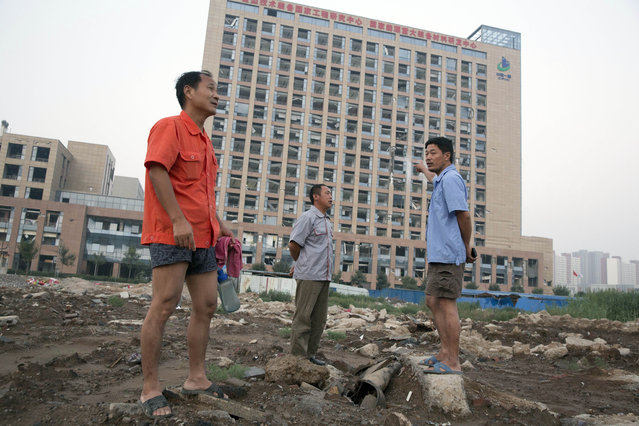 Workers walk near a building with windows shattered by the shockwave from a nearby explosion in northeastern China's Tianjin municipality, Thursday, August 13, 2015. (Photo by Ng Han Guan/AP Photo)