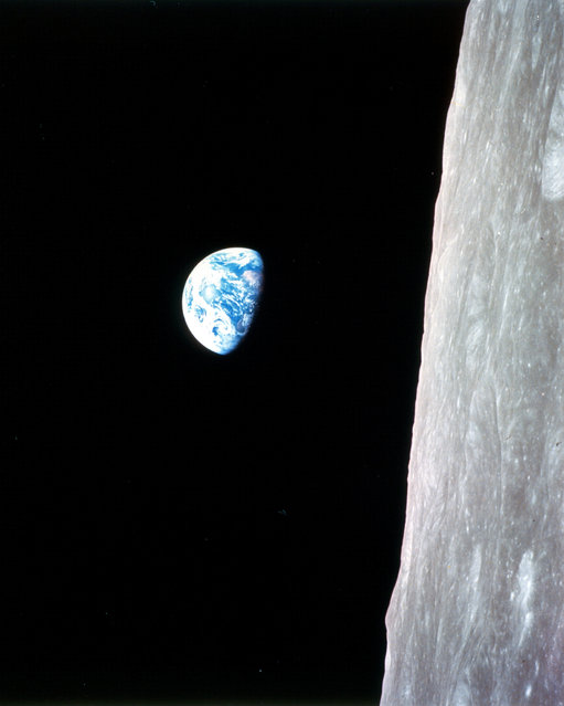This view of the rising Earth greeted the Apollo 8 astronauts as they came from behind the Moon after the fourth nearside orbit. The photo is displayed here in its original orientation, though it is more commonly viewed with the lunar surface at the bottom of the photo. Earth is about five degrees left of the horizon in the photo. The unnamed surface features on the left are near the eastern limb of the Moon as viewed from Earth. The lunar horizon is approximately 780 kilometers from the spacecraft. (Photo by NASA)