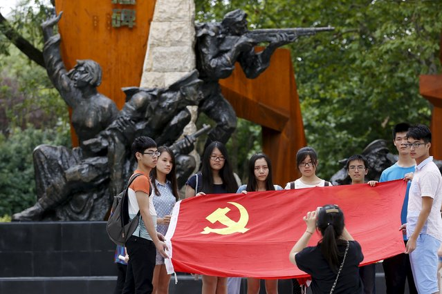 College students hold a flag of the Communist Party of China in front of a sculpture during a media trip at the Shanghai Songhu Campaign Memorial Hall in Shanghai, August 13, 2015. (Photo by Aly Song/Reuters)