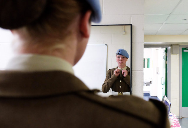 Junior Soldier Emma Laidlaw, 17, from Glasgow makes final adjustments to her uniform ahead of her graduation parade at the Army Foundation College on August 13, 2015 in Harrogate, England. Over 600 Junior Soldiers aged between 16 and 18 graduated at the Army Foundation College following a year of undergoing military skills training, vocational qualifications and City and Guilds apprenticeships. (Photo by Ian Forsyth/Getty Images)