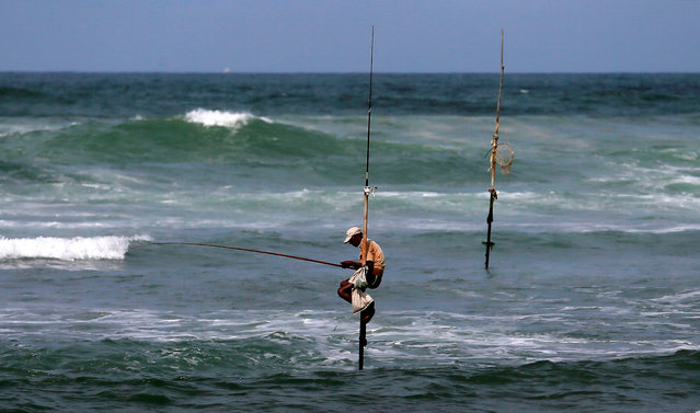 A fisherman waits to catch fish as he sits atop a stilt in the sea in Koggala, Sri Lanka on July 4, 2019. (Photo by Dinuka Liyanawatte/Reuters)