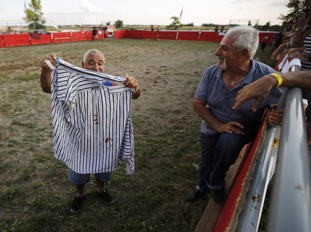 """Bolino Silveira (L), who emigrated from the Azores to Mississauga, Ontario, shows friends a torn and bloodied shirt after he fell at an Azorean """"tourada a corda"""" (bullfight by rope) in Brampton, Ontario August 15, 2015. (Photo by Chris Helgren/Reuters)"""