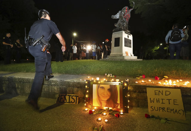 Police move in to Piedmont Park to prevent protesters from toppling a Confederate monument with a chain after they spray-painted it, Sunday, August 13, 2017, in Atlanta. The peace monument at the 14th Street entrance depicts a angel of peace stilling the hand of a Confederate soldier about to fire his rifle. Protesters decrying hatred and racism converged around the country on Sunday, saying they felt compelled to counteract the white supremacist rally that spiraled into deadly violence in Virginia. (Photo by Curtis Compton/Atlanta Journal-Constitution via AP Photo)