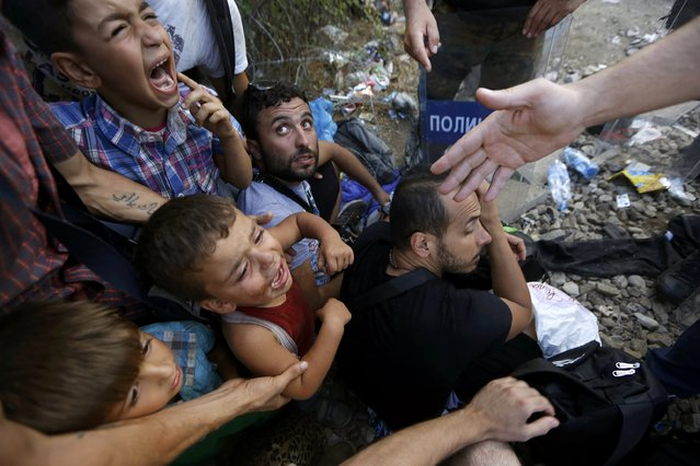 Syrian refugee children scream as they are siting in front of Macedonian riot police at the Greek-Macedonian border, near the village of Idomeni, August 21, 2015. (Photo by Yannis Behrakis/Reuters)
