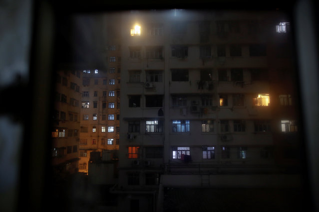 An apartment block is seen through the window of a space where people live in wooden boxes in Hong Kong October 9, 2012. (Photo by Damir Sagolj/Reuters)