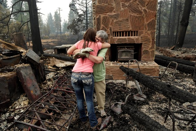 Donna Garner, right, embraces former employee Napua Gonsales-Merck while they shift through the remains of the Fireside Village, a restaurant and shop owned by the Garners for over 30 years, in the aftermath of the Eiler Fire on Tuesday, August 5, 2014, in Hat Creek, Calif. Light rain and higher humidity are helping crews make progress in their fight against two wildfires in the Northern California forest that are just miles apart. (Photo by Marcio Jose Sanchez/AP Photo)