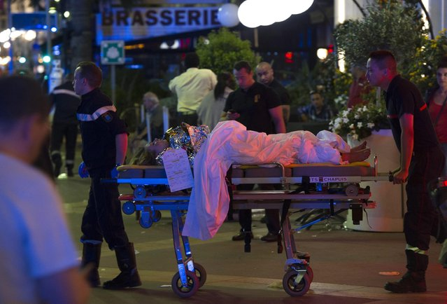 Wounded people are evacuated from the scene where a truck crashed into the crowd during the Bastille Day celebrations in Nice, France, 14 July 2016. (Photo by Olivier Anrigo/EPA)