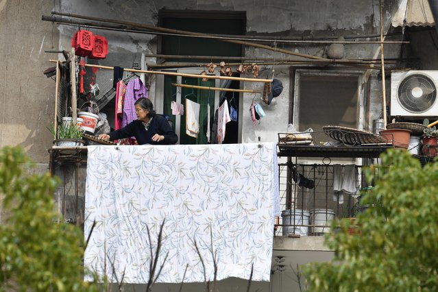 A woman places food out on a balcony to dry at a residential compound in Wuhan, the epicenter of the coronavirus outbreak, Hubei province, China, March 10, 2020. (Photo by Reuters/China Stringer Network)
