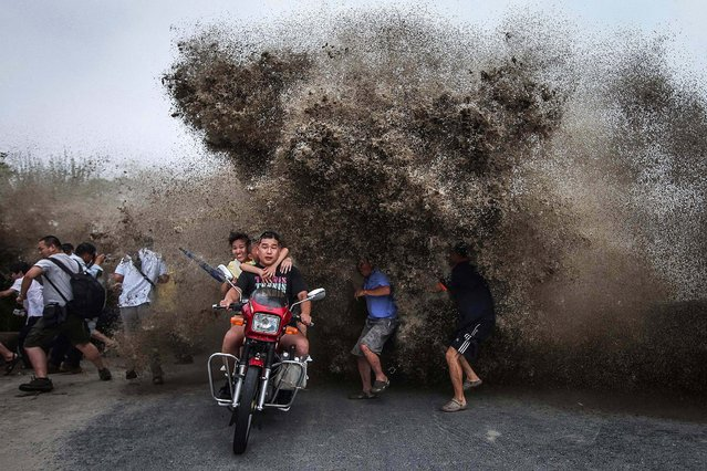 Bikers and spectators gathered to watch the Qiantang tidal bore run as a wave crashes inland on the banks of the Qiantang River in Hangzhou, China, on August 13, 2014. (Photo by Associated Press)