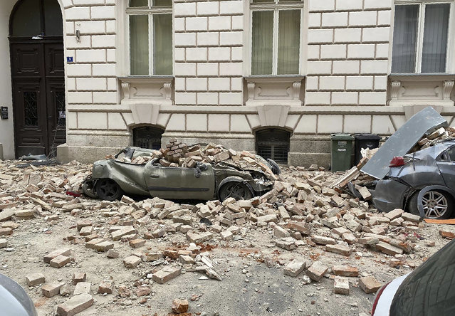A car is crushed by falling debris after an earthquake in Zagreb, Croatia, Sunday, March 22, 2020. A strong earthquake shook Croatia and its capital on Sunday, causing widespread damage and panic. (Photo by Filip Horvat/AP Photo)