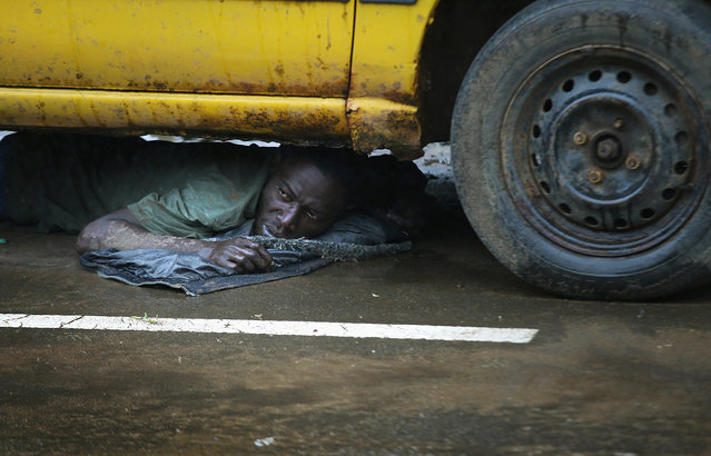 A man lies under a car after being put there in detention by the Liberian army on the second day of the government's Ebola quarantine on their neighborhood of West Point on August 21, 2014 in Monrovia, Liberia. An army officer said that he was showing symptoms of Ebola and was caught trying to escape from West Point. (Photo by John Moore/Getty Images)