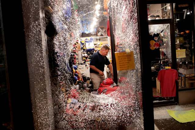 A worker cleans up broken glass from a window smashed during a protest of the acquittal of former St. Louis police officer Jason Stockley on September 16, 2017 in St. Louis, Missouri. Dozens of business windows were smashed and at least two police cars were damaged during a second day of protests following the acquittal of Stockley, who was been charged with first-degree murder last year following the 2011 on-duty shooting of Anthony Lamar Smith. (Photo by Scott Olson/Getty Images)