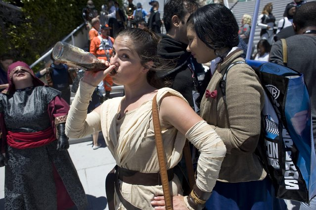 Ginny Espinoza (C), dressed as Star Wars fictional character Rey, drinks a soda after participating in a group photo outside Comic Con 2016 on 22 July 2016 in San Diego, California, USA. (Photo by David Maung/EPA)