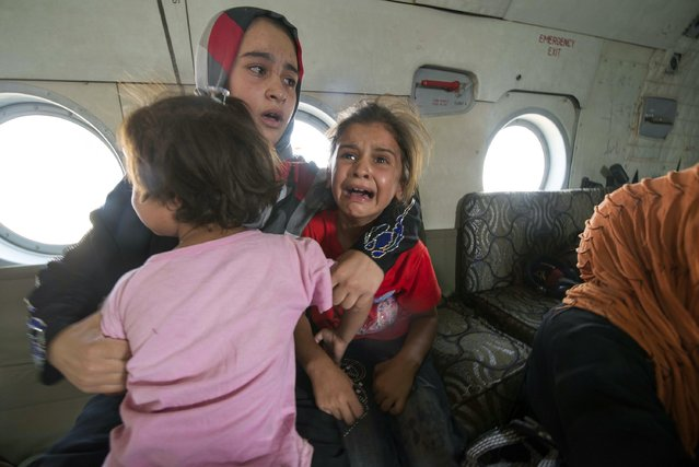 A woman and children react in a military helicopter after being evacuated by Iraqi forces from Amerli, north of Baghdad August 29, 2014. A home to around 180,000 people, mostly Turkmen Shi'ites, the small town of Amerli, north of Baghdad is still holding out against repeated attacks by Islamic State fighters despite the fall of all the 34 villages surrounding it. (Photo by Reuters/Stringer)