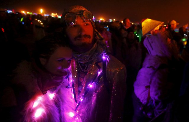 """Hannah Neil (L) and Austin Bennett embrace as they watch the Man burn during the Burning Man 2015 """"Carnival of Mirrors"""" arts and music festival in the Black Rock Desert of Nevada September 5, 2015. (Photo by Jim Urquhart/Reuters)"""