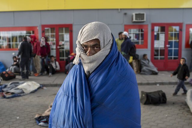 A migrant from Syria tries to warm himself at a gas station while waiting to be transported to a reception camp near the village of Roszke, Hungary September 6, 2015. (Photo by Marko Djurica/Reuters)
