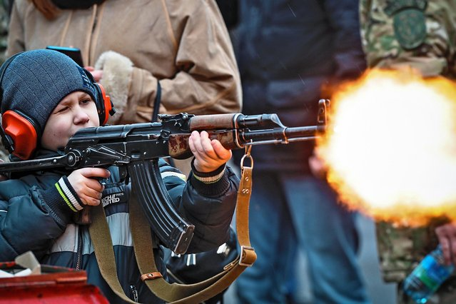 A boy fires blanks from a Kalashnikov rifle, during Maslenitsa celebrations, or Shrovetide, to say farewell to winter in Minsk, Belarus, Sunday, March 1, 2020. Maslenitsa is a traditional Russian and Belarusian holiday marking the end of winter that dates back to pagan times. (Photo by Sergei Grits/AP Photo)